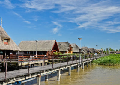 Houses on legs behind a long pier on a lake