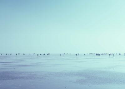 People walking on a mass body of a frozen water