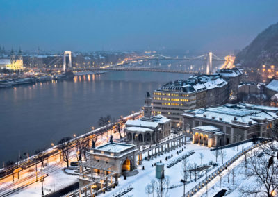 Snow covered city with a river and bridges